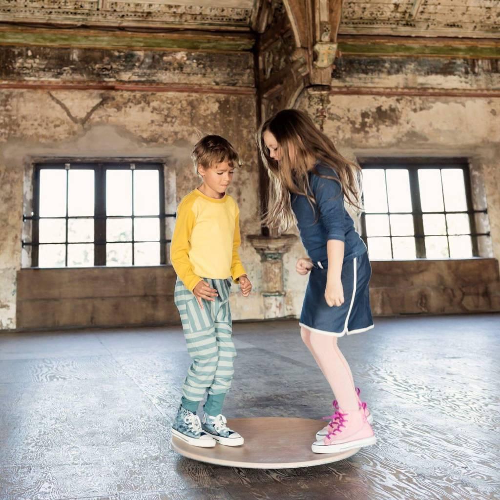 niños jugando en tabla equilibrio redonda wobbel